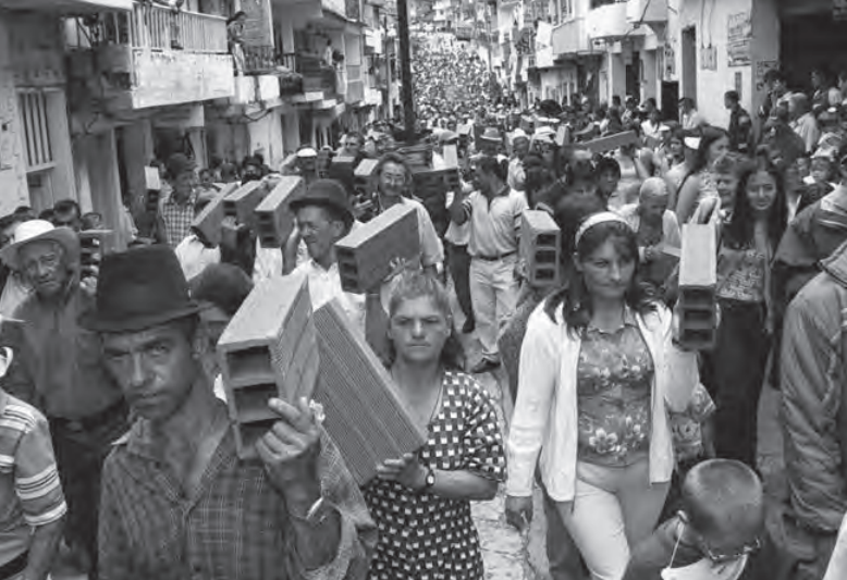 Diez meses después de la toma armada de la guerrilla de las FARC que destruyó cerca de 250 viviendas y dejó 5 policías y 18 civiles muertos, la población con apoyo de la gobernación de Antioquia, realizó la marcha del ladrillo para reconstruir su pueblo. Granada, octubre de 2001. Jesús Abad Colorado