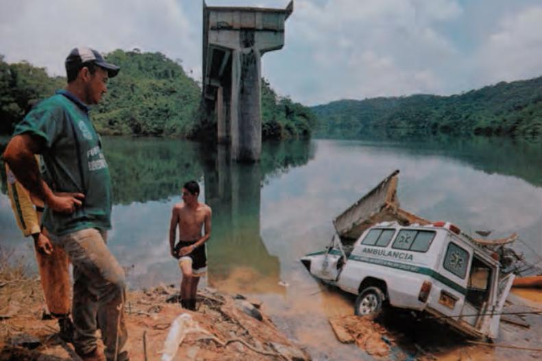 """Una mujer en embarazo que viajaba en ambulancia rumbo a Medellín, murió junto a la enfermera que la acompañaba al caer en la represa de """"playas"""" porque minutos antes la guerrilla de las FARC había destruido el puente que une a los municipios de San Rafael y San Carlos. Fotografía: Javier Agudelo, El Tiempo © 2002."""