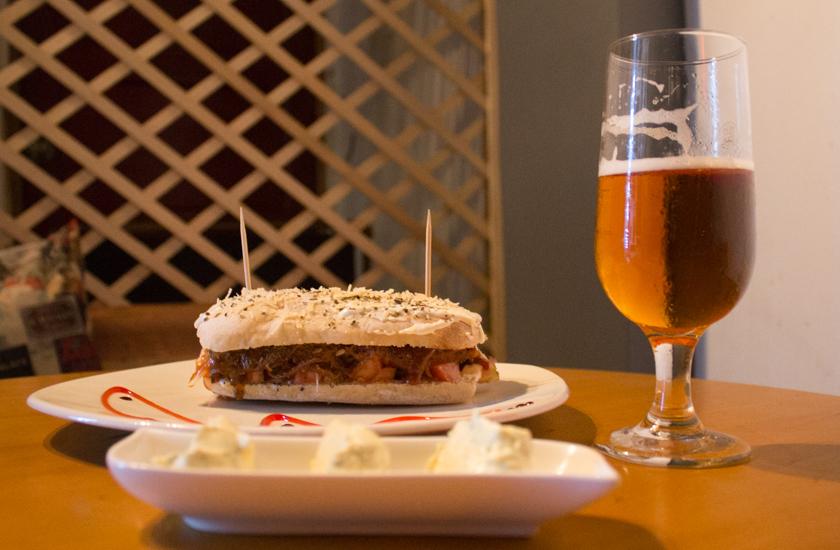 Sándwich artesanal de pan arabe en forma cuadrada con carne desmechada en salsa napolitana
